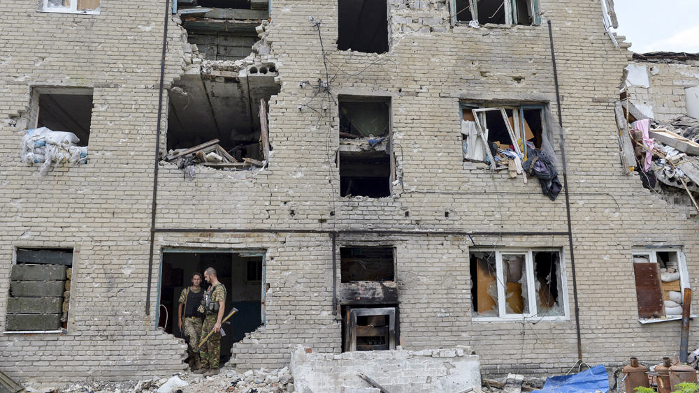Members of the Ukrainian armed forces stay at a building damaged in fighting with pro-Russian separatists in Pesky village, near Donetsk, Ukraine, July 6, 2015. REUTERS/Oleksandr Klymenko TPX IMAGES OF THE DAY - RTX1J9WJ