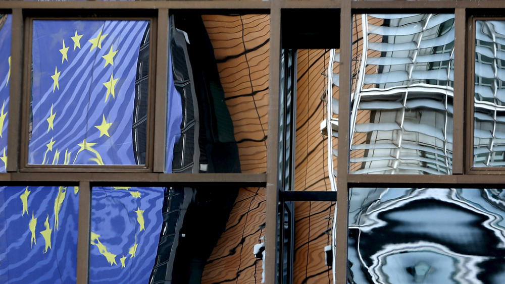 The facade of the European Commission headquarters is reflected in the windows of the EU Council building in Brussels, Belgium, May 20, 2015. REUTERS/Francois Lenoir - RTX1DT61