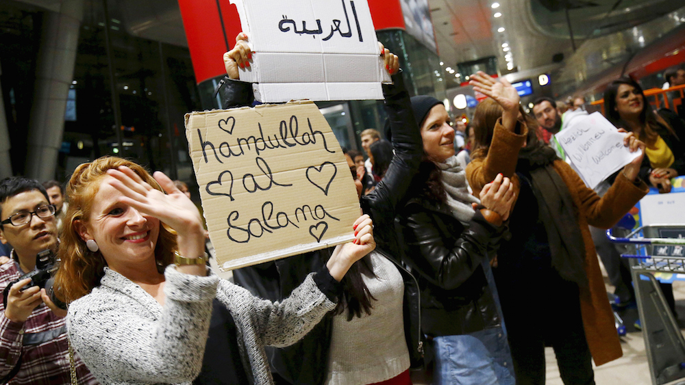 Wellwishers applaud and hold up signs welcoming migrants as Syrian families disembark a train that departed from Budapest's Keleti station at the railway station of the airport in Frankfurt, Germany, early morning September 6, 2015. Austria and Germany threw open their borders to thousands of exhausted migrants on Saturday, bussed to the Hungarian border by a right-wing government that had tried to stop them but was overwhelmed by the sheer numbers reaching Europe's frontiers. REUTERS/Kai Pfaffenbach - RTX1RABZ