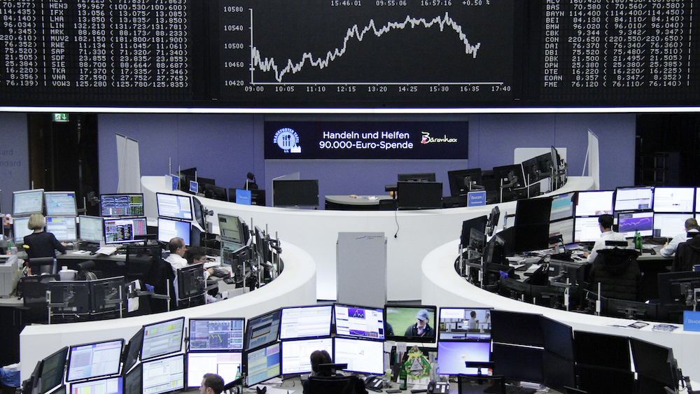 Traders work at their desks in front of the German share price index DAX board at the stock exchange in Frankfurt, Germany, December 16, 2015. REUTERS/Staff - RTX1YYZD