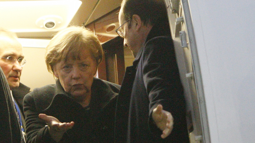 Germany's Chancellor Angela Merkel (L) and France's President Francois Hollande walk out after a meeting inside a plane at an airport near Minsk, February 11, 2015. The leaders of France, Germany, Russia and Ukraine were due to attend a peace summit on Wednesday, but Ukraine's pro-Moscow separatists diminished the chance of a deal by launching some of the war's worst fighting in an assault on a government garrison. REUTERS/Valentyn Ogirenko (BELARUS - Tags: POLITICS TRANSPORT CIVIL UNREST CONFLICT) - RTR4P6O1